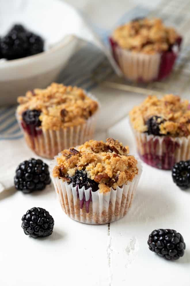 three muffins sitting on a white table with one muffin sitting on a cooling rack and fresh berries on the table