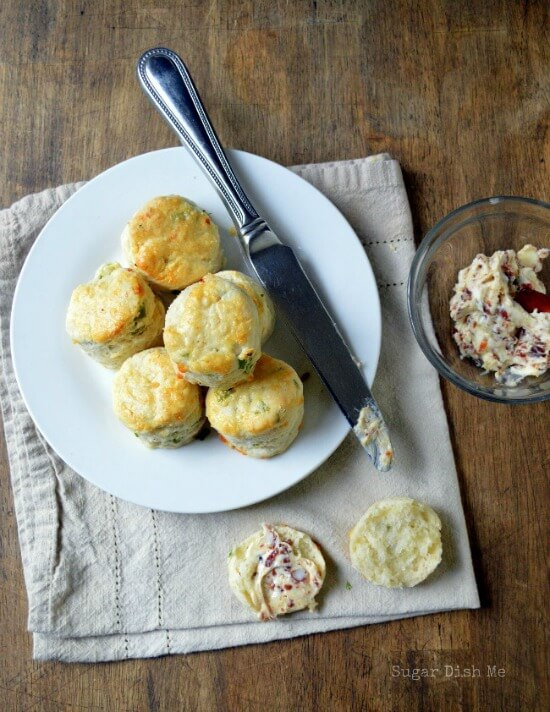 A few cheese scones on a plate with a side of bacon butter.