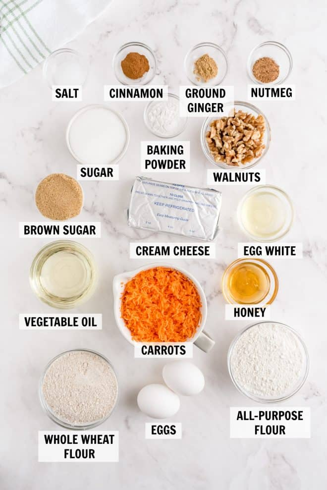 ingredients for carrot loaf on a white backdrop
