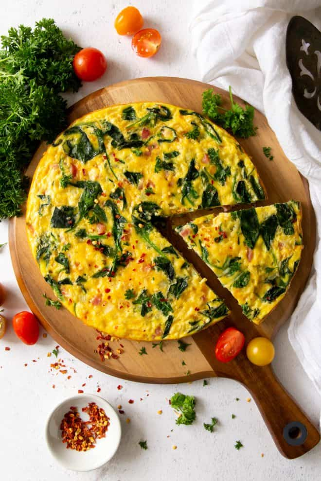 ham and spinach frittata on a cutting board with tomatoes and parsley on the side as garnish