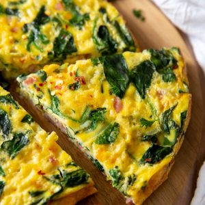 a slice of ham and spinach frittata sitting on a cutting board