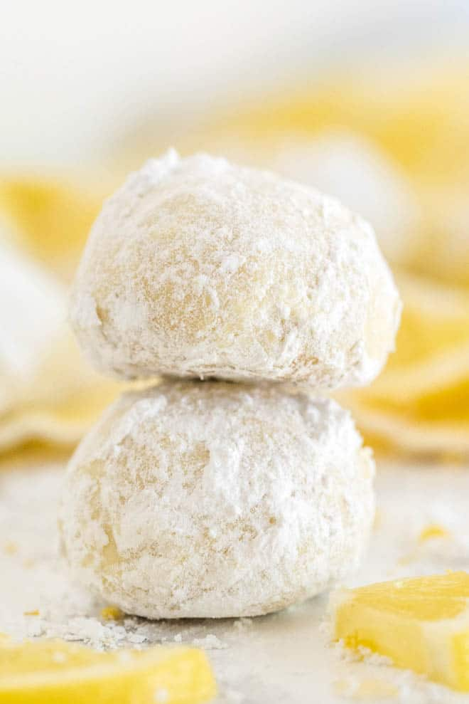 two lemon tea cookies stacked on top of each other with a yellow napkin in the background