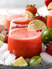 a clear glass with a frozen strawberry margarita in it, garnished with lime and strawberry
