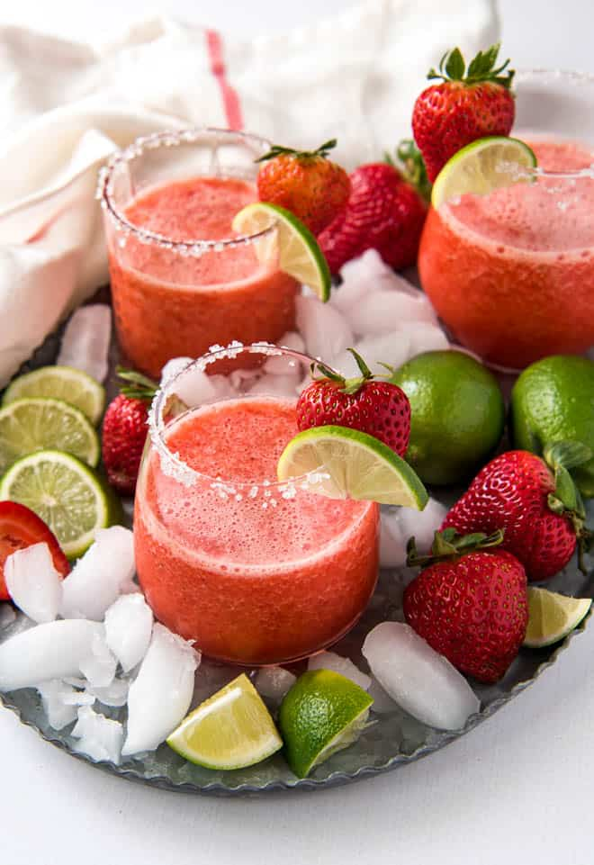 three glasses of strawberry margarita sitting on a serving tray with strawberries and limes