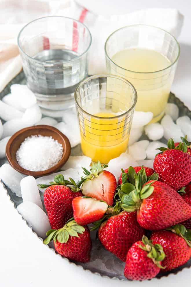 orange juice lime juice, salt, tequila, strawberries and ice sitting on a grey metal serving tray