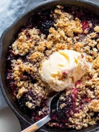 A skillet of warm berry crisp with a scoop of vanilla ice cream.