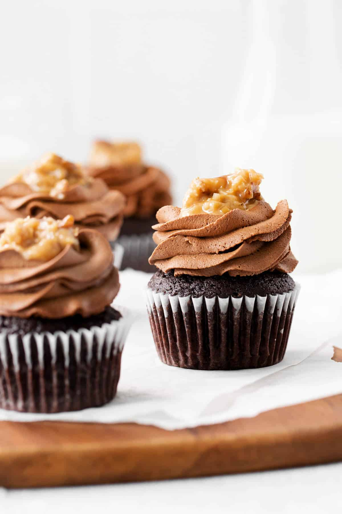 three german chocolate cupcakes sitting on a piece of parchment paper