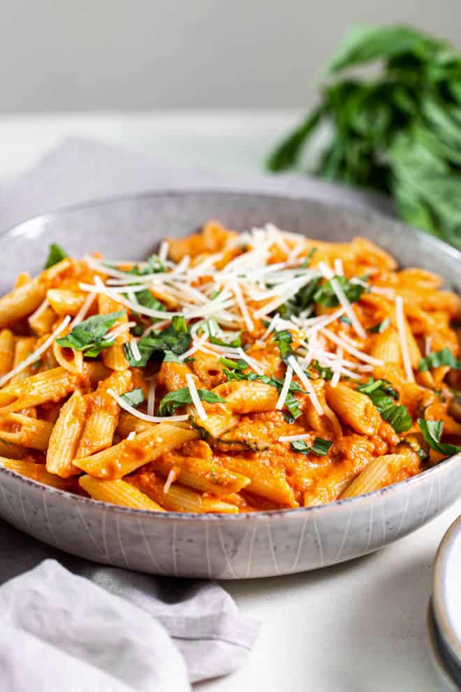 large bowl of tomato basil pasta with cheese and basil on top