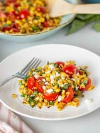 sautéed corn with tomatoes, basil and feta cheese on a plate