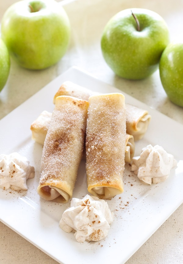 baked apple pie egg rolls on a plate with cinnamon whipped cream