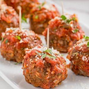 mozzarella stuffed meatballs sitting on a white place