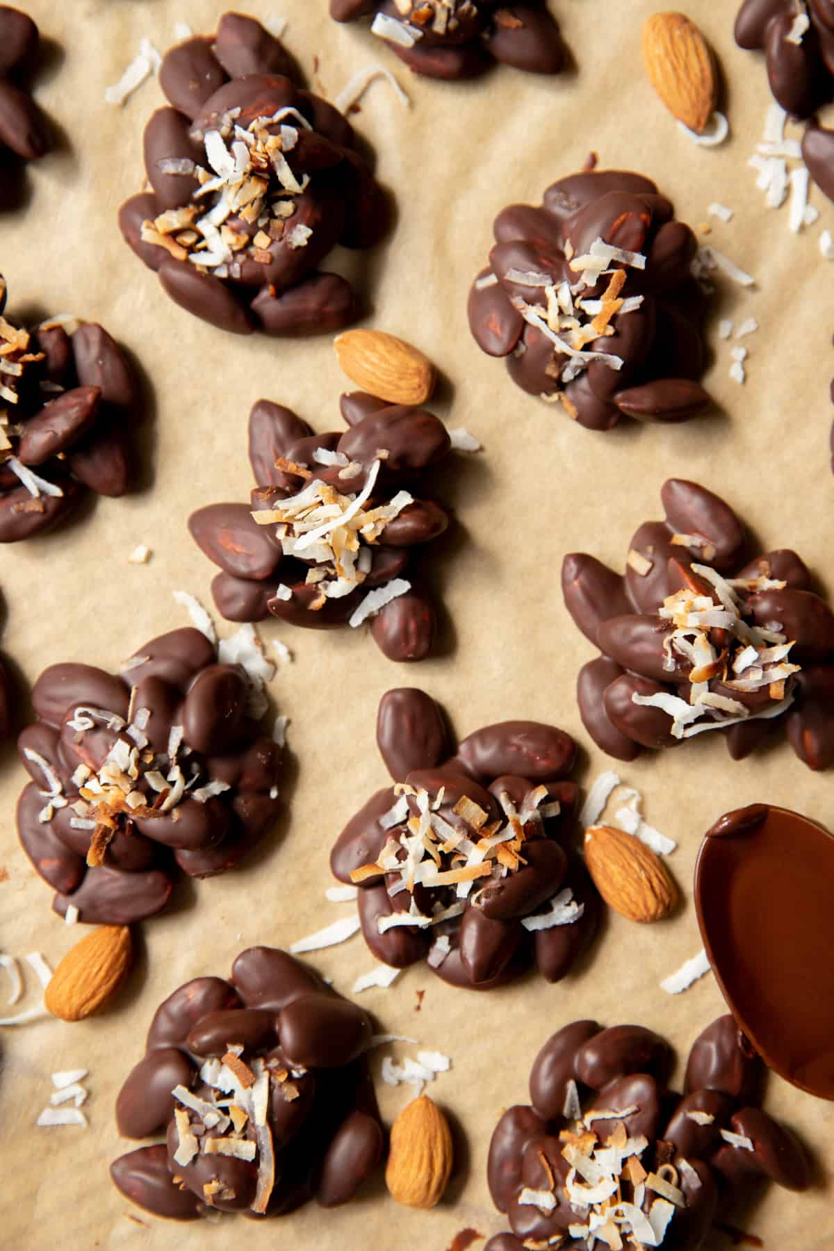dark chocolate almond clusters on a piece of parchment paper with shredded coconut on top