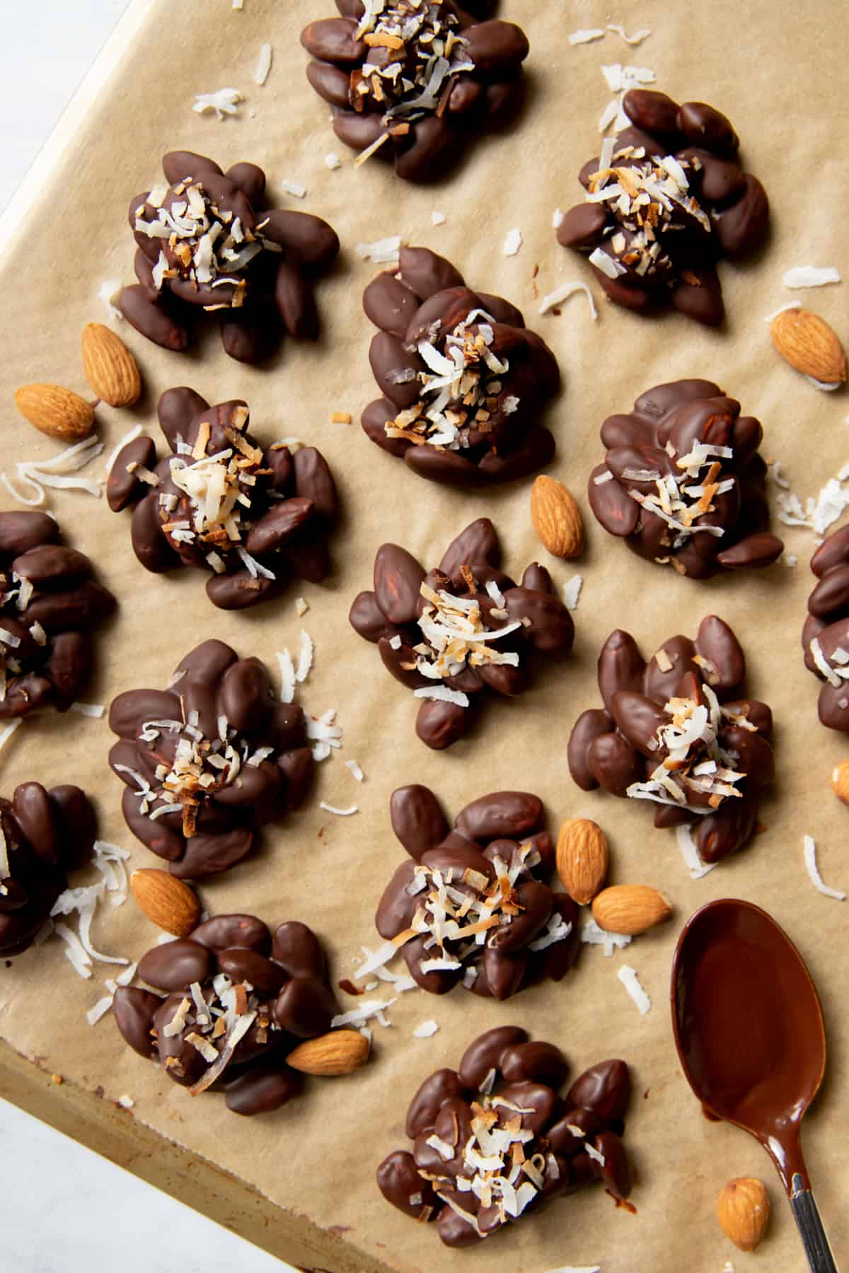 many chocolate almond clusters on a baking pan with raw almonds scattered around