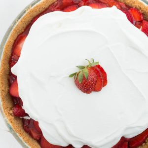 Strawberry Pie is made with a few ingredients and is full of fresh strawberry flavor! Fresh sliced strawberries are layered over a graham cracker crust and topped with whipped cream!