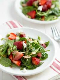 Strawberry spinach asparagus salad on a white plate on a white table.
