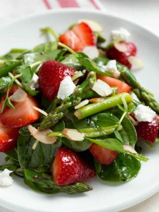 A large plate of spinach and strawberry salad.