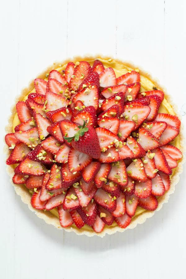 Strawberry Pistachio Cardamom Tart is made with a lemon coconut crust, cardamom pastry cream, fresh strawberries and pistachios! It is gluten free and dairy free too!