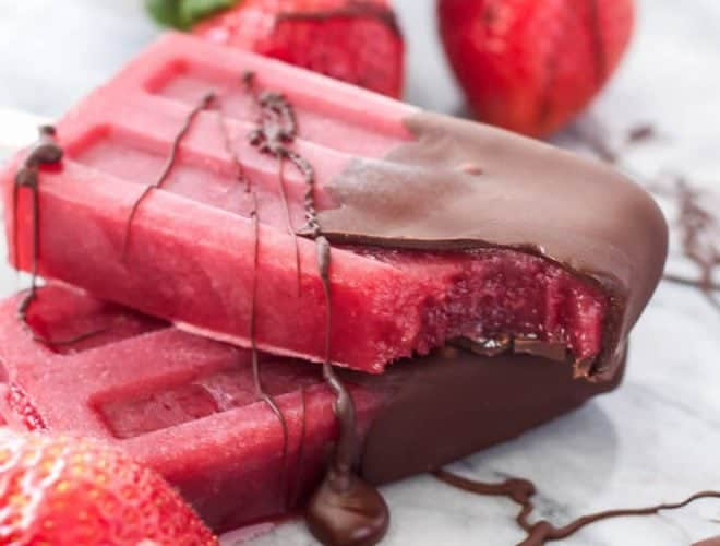 Strawberry red wine popsicles with chocolate sauce on them.