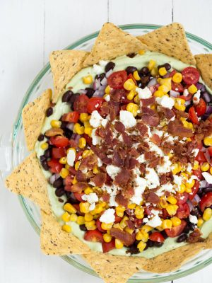 Easy Party Dip with Avocado Greek yogurt is a delicious 7 layer dip made with black beans, tomatoes, bacon and more!