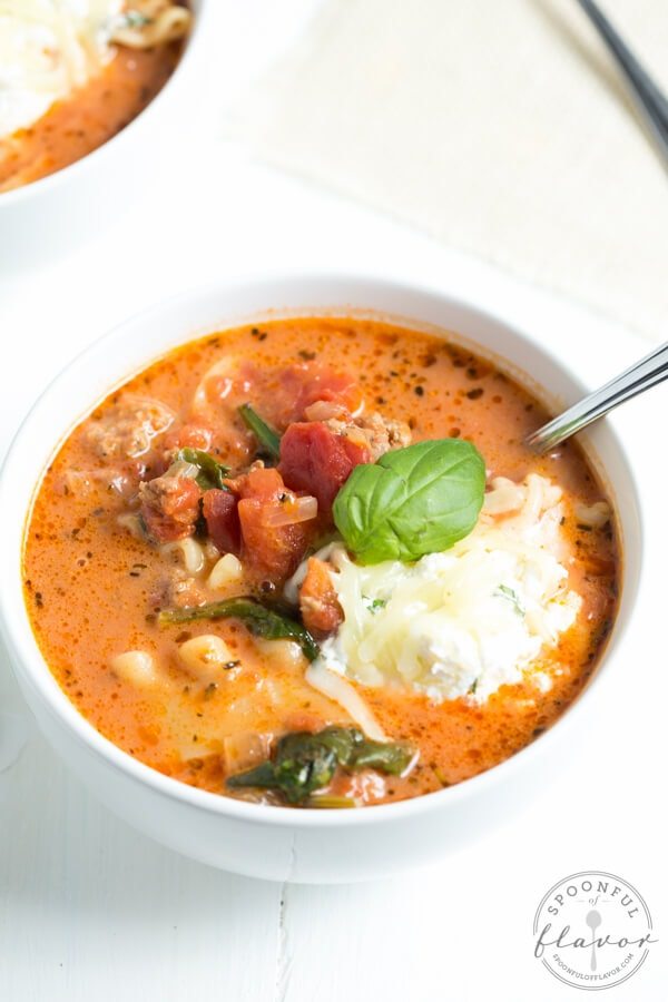 Spinach Lasagna Soup is your favorite comfort food served in a bowl and topped with cheesy goodness. Made with fresh spinach, tomatoes, Italian sausage, lasagna, herbs and more, this soup is perfect for the entire family!