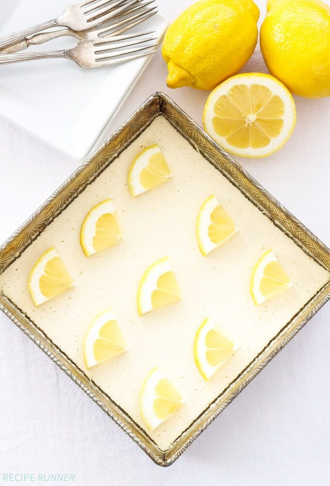 A square metal pan filled with lemon cheesecake and lemon slices on top