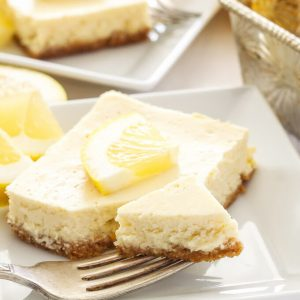 A fork on a white plate with a slice of lemon cheesecake bar