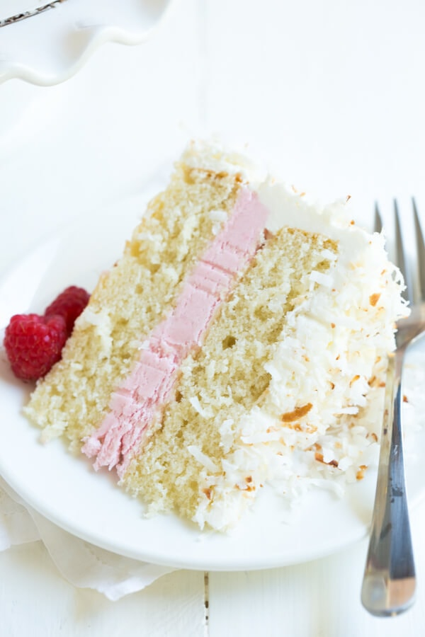 Coconut Cake with raspberry buttercream filling and marshmallow frosting is perfect for birthdays, holidays and celebrations! Made with fresh raspberry puree.
