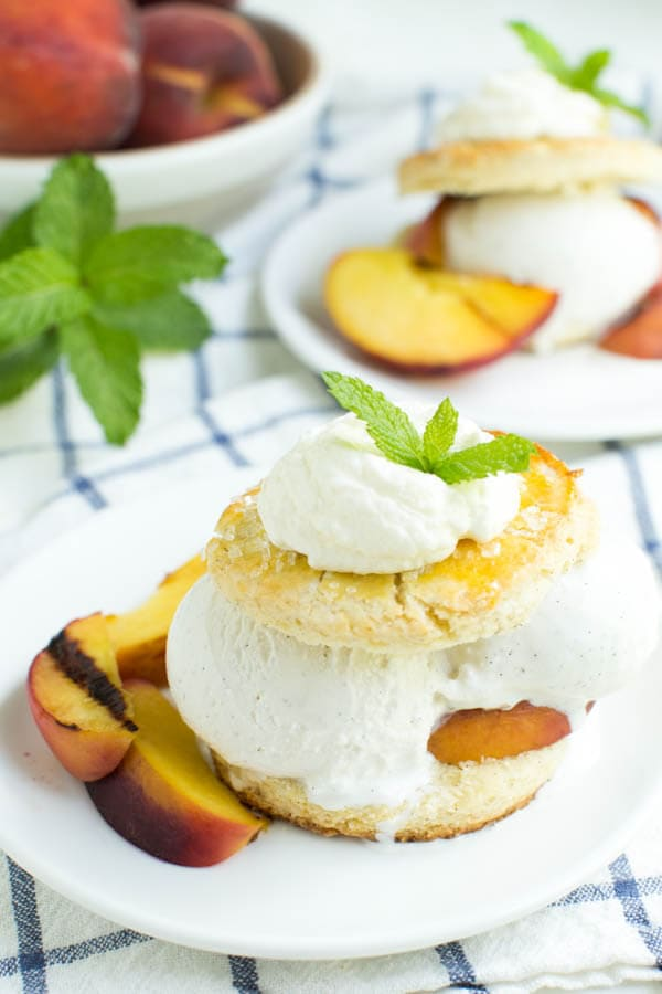 Grilled Peaches and Cream Shortcake is a unique twist on a favorite classic dessert. Grilled peaches are served with vanilla bean shortcake and a scoop of ice cream!