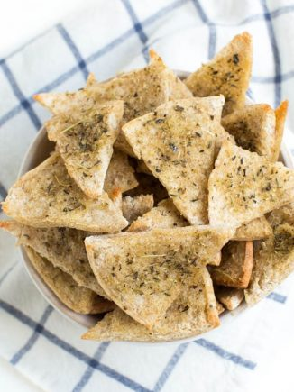 A large bowl of baked seasoned pita chips.