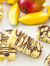 Chocolate Drizzled Mango Yogurt Pops | A sweet, frozen treat to cool off with on a hot day! Made with healthy ingredients they're perfect for a snack, dessert or even breakfast!