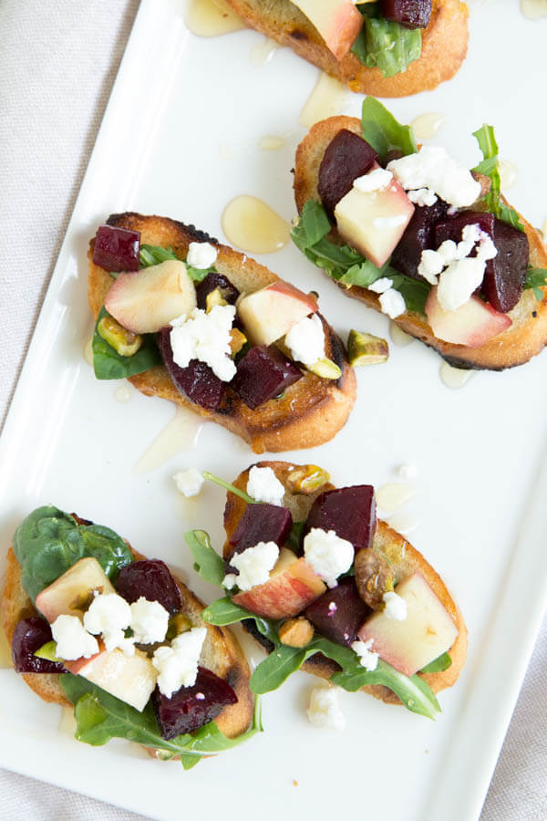 Grilled Apple, Beet and Arugula Crostini is a fresh appetizer made with beets, apples, greens, pistachios, goat cheese and a drizzle of honey!
