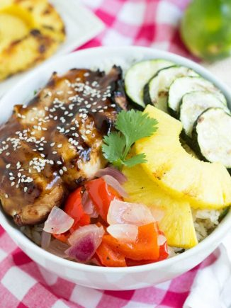 teriyaki chicken, grilled zucchini, pineapple and vegetables in a bowl over rice sitting on a pink checker napkin