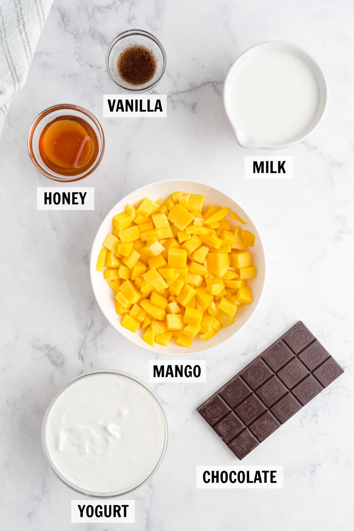 all of the ingredients for mango popsicles on a white countertop