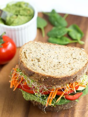 Lemon Spinach Hummus, spinach, carrots, cucumber, tomato, sprouts and red peppers are piled high on top of freshly baked bread to create the ultimate veggie hummus sandwich!