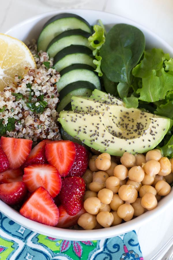 Nourish yourself with a berry green Buddha bowl packed with protein, fresh greens, vegetables, berries and topped with a creamy lemon avocado kale mint dressing!