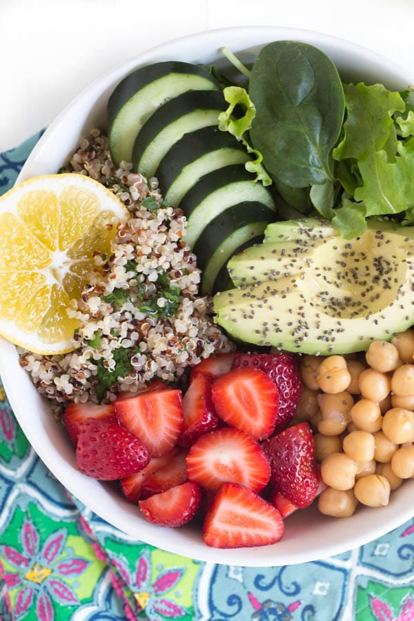 Nourish yourself with a berry green Buddha bowl with lemon avocado kale mint dressing!