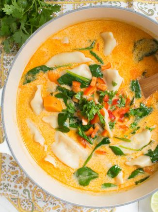 a large pot of potsticker soup with fresh vegetables