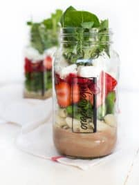 Six ingredients are layered in a mason jar to create a fresh and flavorful Spring Green Mason Jar Salad with Strawberries! Pack the mason jar for on-the-go or enjoy an easy lunch at home.