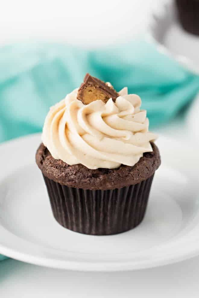 one chocolate peanut butter cupcake with frosting sitting on a white plate