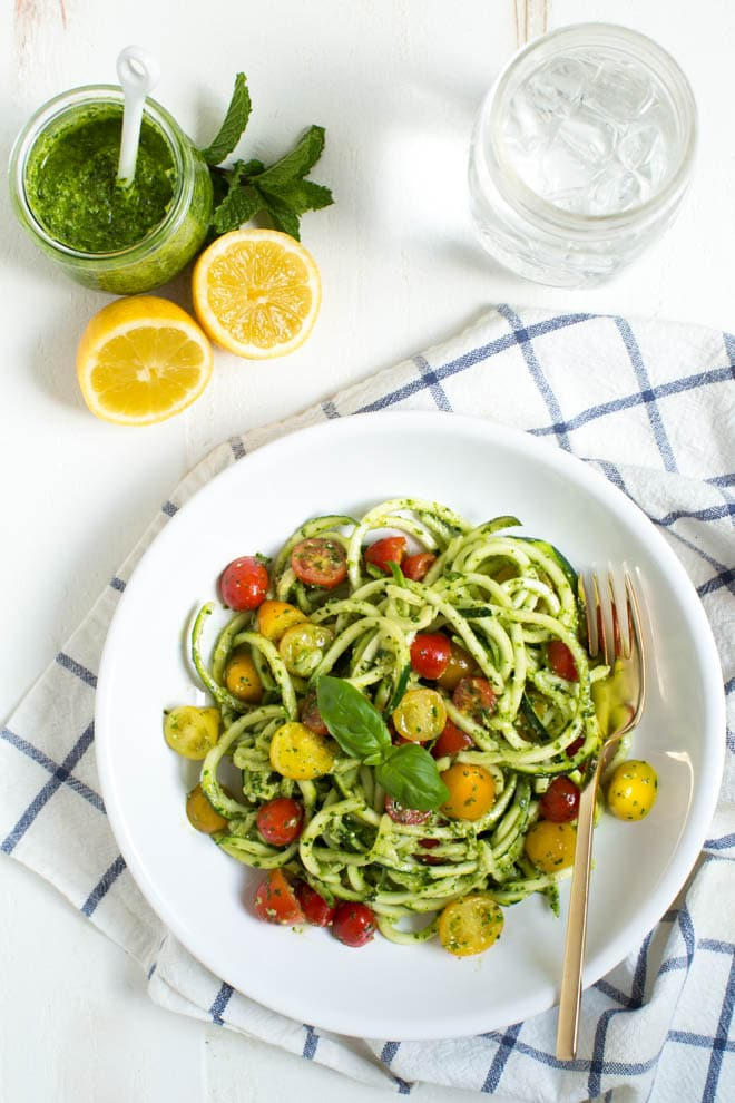 Kale Mint Pesto Zoodles is a quick and easy dinner recipe that comes together in less than 15 minutes! Spiralized zucchini noodles are mixed with a homemade kale mint pesto and cherry tomatoes.