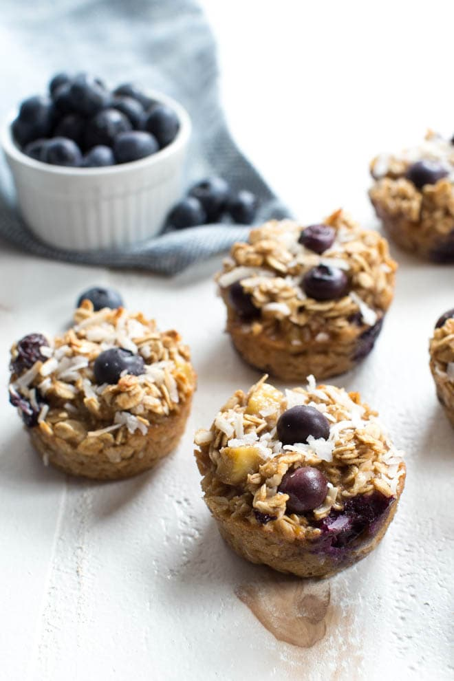 baked oatmeal cups with blueberries sitting on a white tabletop with a cup of  blueberries on the side
