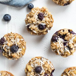 baked oatmeal cups with blueberries sitting on a white tabletop