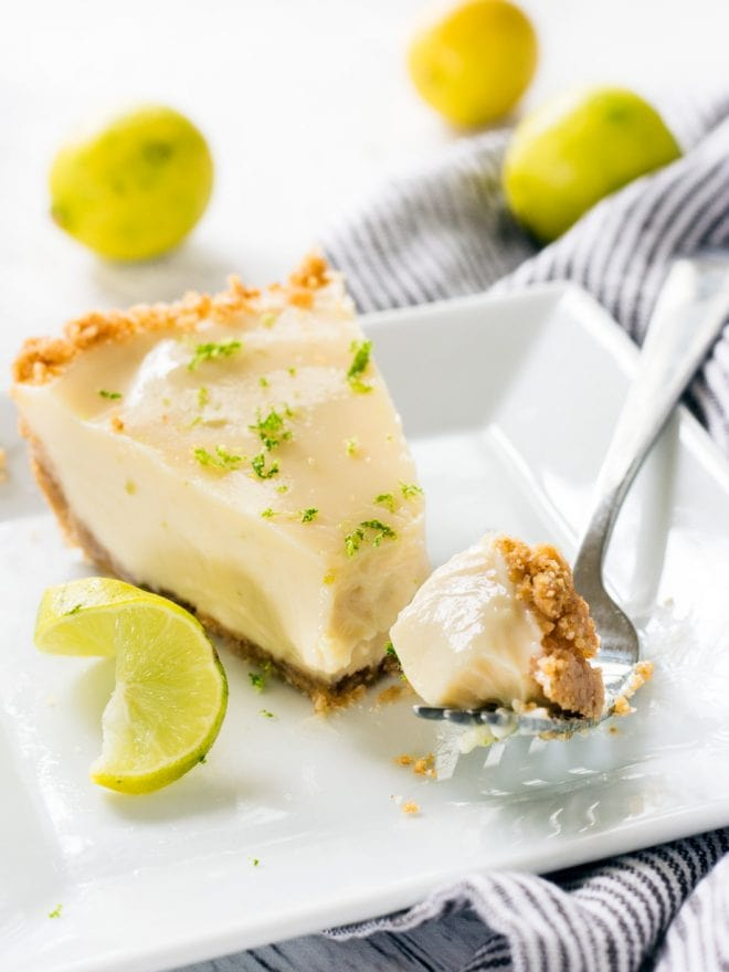 A slice of key lime pie with a fork on a plate.