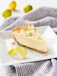 One slice of key lime pie sitting on a white place.