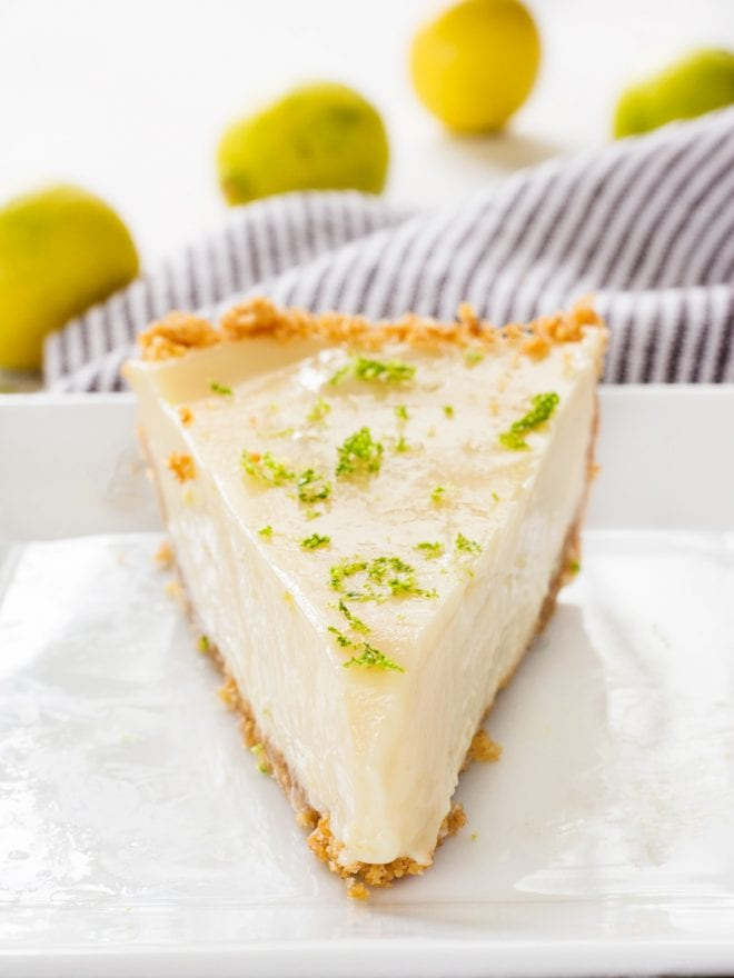 A large slice of key lime pie sitting on a white plate with lime zest on top.