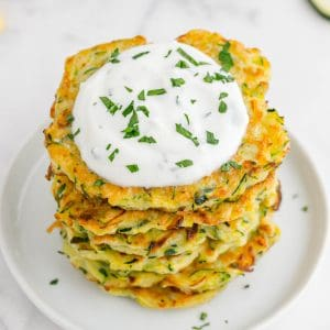 a plate of zuchinni fritters with yogurt dip on top