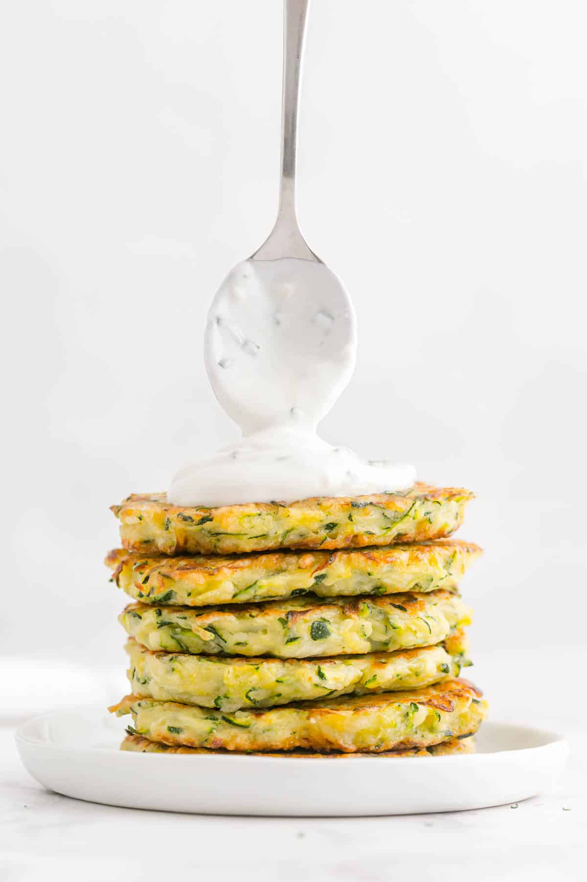 stack of zucchini fritters with a spoonful of yogurt dip on top