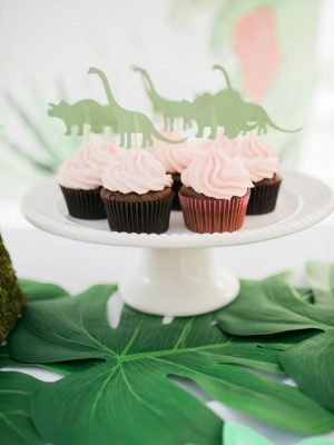 A dino-mingo kids birthday party combines flamingos and dinosaurs to create a fun theme that everyone will love! The party features a mimosa bar, dinosaur footprint cookies, flamingo cookies, chocolate cupcakes with strawberry frosting and other tasty creations.