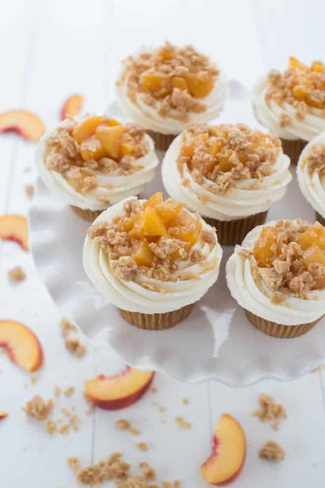 Peach Pie Cupcakes are a fun twist on a classic dessert! Light vanilla bean cupcakes are topped with homemade peach pie filling, vanilla buttercream frosting and baked crumb topping.
