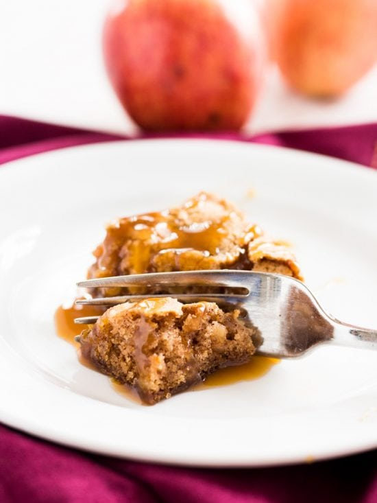 Each bite of this caramel apple cake has pieces of chopped up apple and a drizzle of caramel. | www.ifyougiveablondeakitchen.com